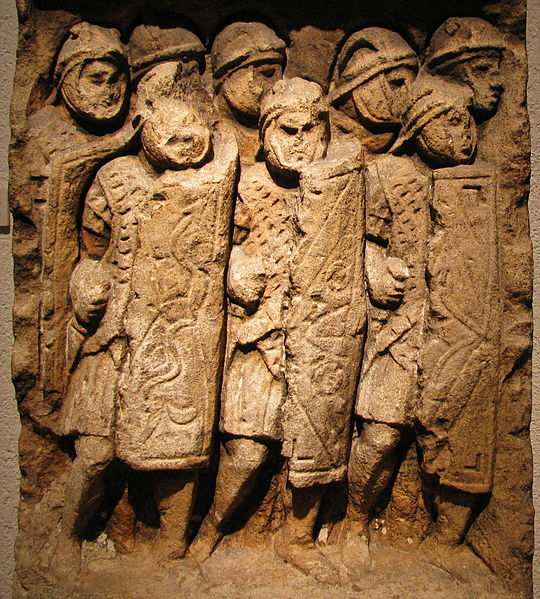Wall carving of Roman soldiers with shields and swords.