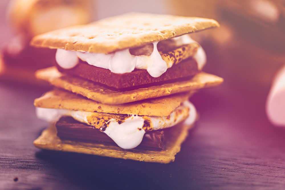 A close up of a couple of s'mores stacked up with melted marshmallow oozing out.