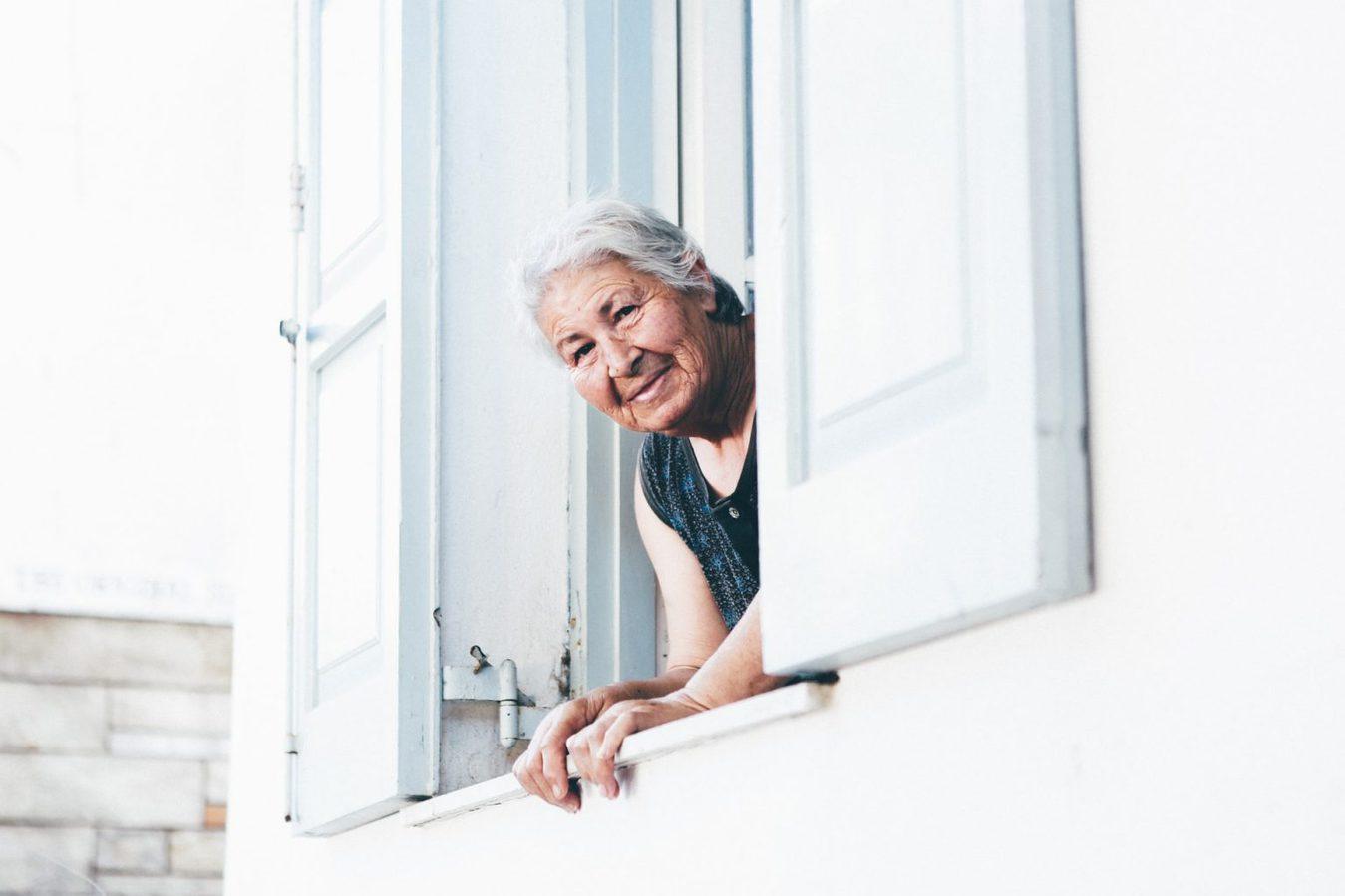 Older woman looking through window