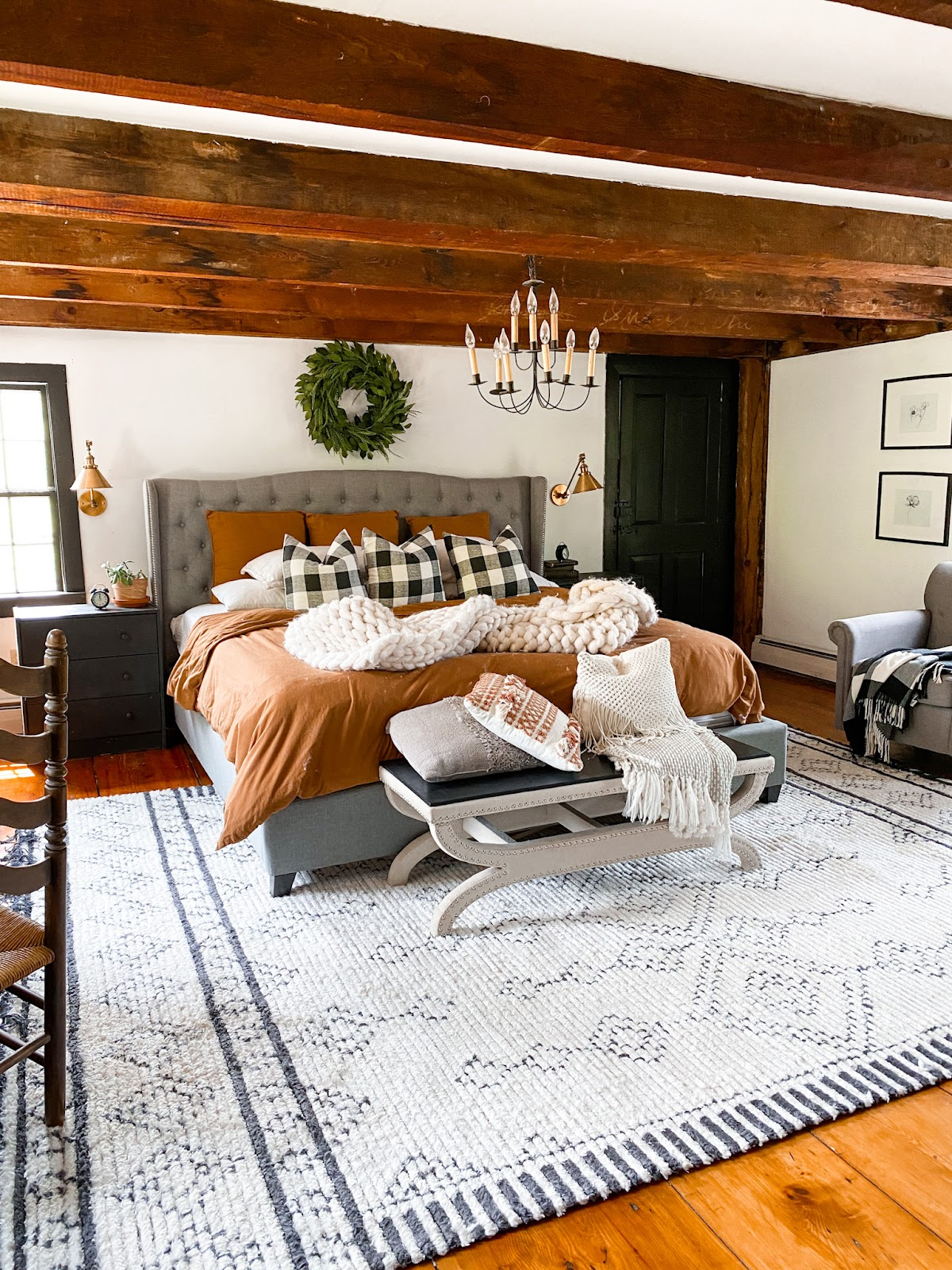 boho bedroom with black accents and a rust comforter