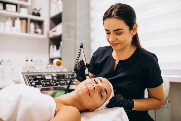 Especialista en medicina estética aplicando tratamiento a paciente