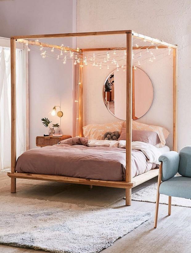 Um quarto com uma cama dossel e um espelho circular.