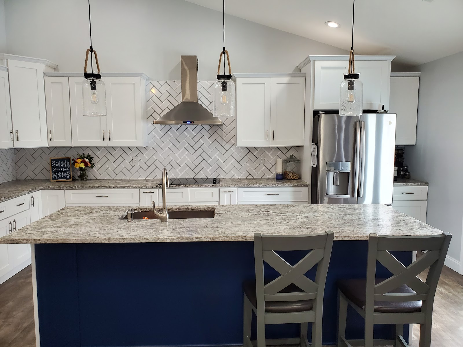 traditional kitchen design with white shaker cabinets, herringbone subway tile backsplash, stainless steel appliances and navy center island