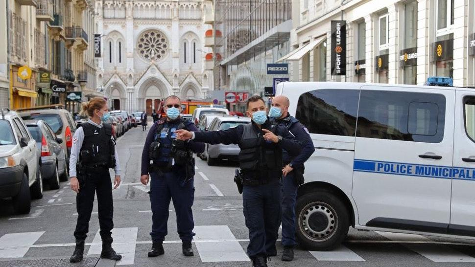 """French policemen stand guard the street leading to the Basilica of Notre-Dame de Nice after a knife attack in Nice on October 29, 2020. - France's national anti-terror prosecutors said Thursday they have opened a murder inquiry after a man killed three people at a basilica in central Nice and wounded several others. The city's mayor, Christian Estrosi, told journalists at the scene that the assailant, detained shortly afterwards by police, """"kept repeating 'Allahu Akbar' (God is Greater) even while under medication."""" He added that President Emmanuel Macron would be arriving shortly in Nice. (Photo by Valery HACHE / AFP) (Photo by VALERY HACHE/AFP via Getty Images)"""