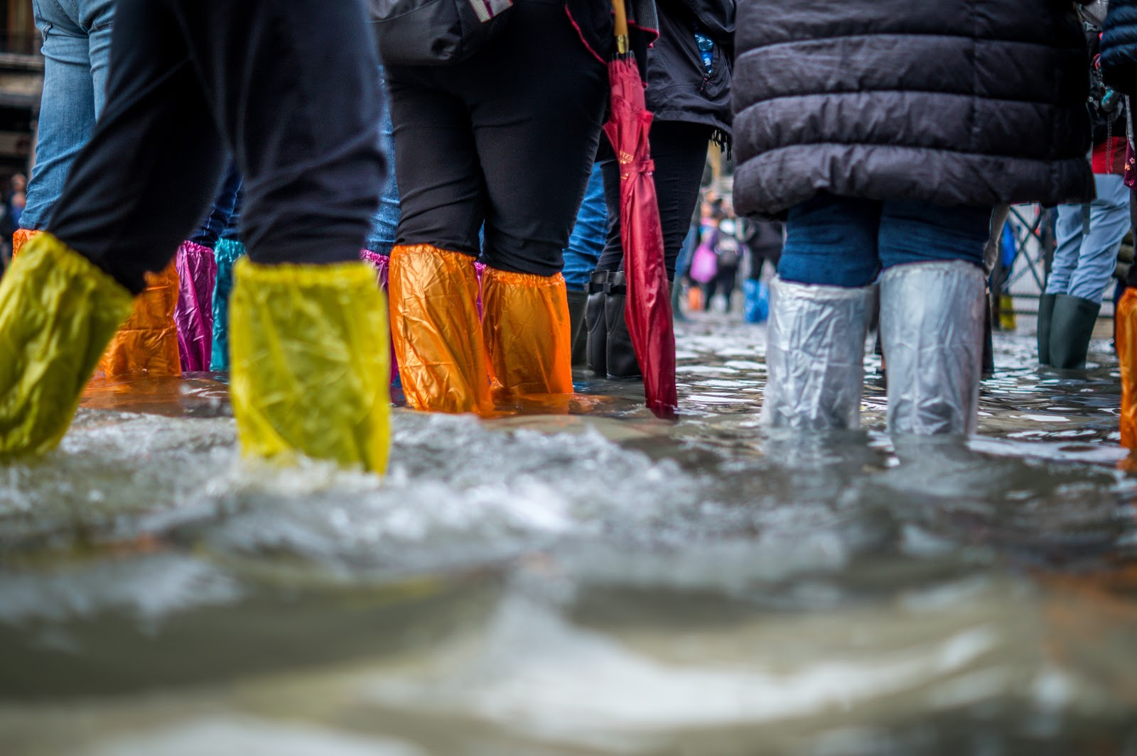 orange, yellow and white plastic foot covers as people walk in a flood