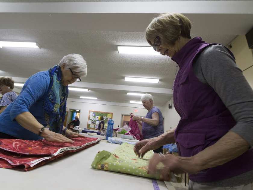 Louise Barr and Colleen Kennedy fold fabric for a group called Grandmothers for Africa, which is hosting a fabric sale on April 22. They say they expect more than 500 people. Proceeds go towards charitable programs for grandmothers in sub-Saharan Africa.