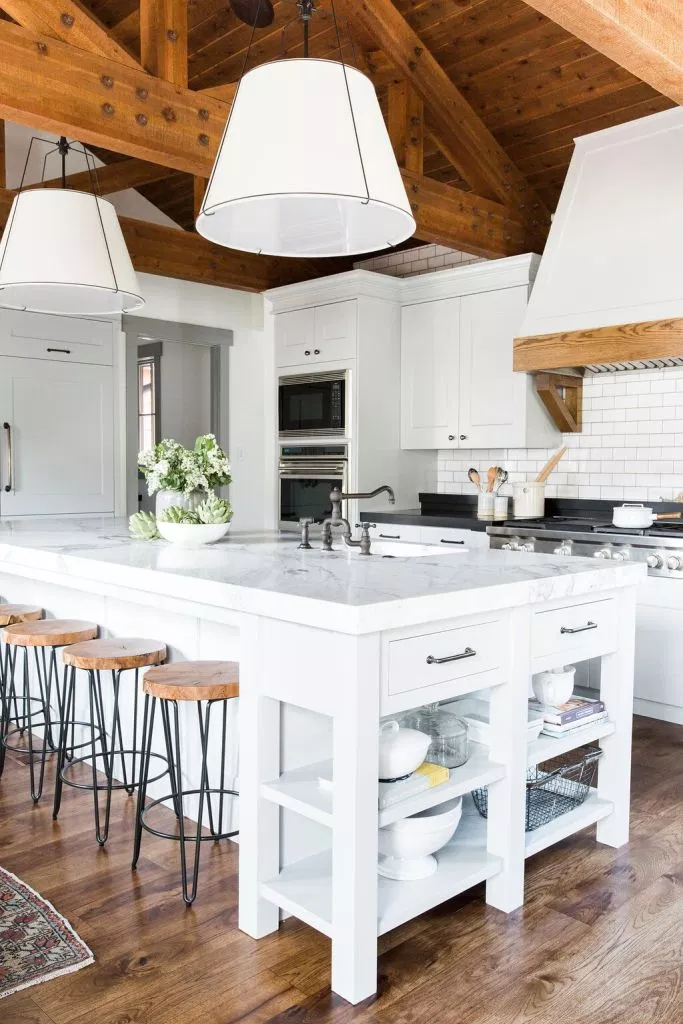 This modern farmhouse kitchen is the perfect gathering place with an oversized white marble island. Wood bar stools and wood overhead beams give the kitchen a weathered look.