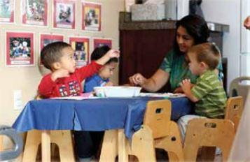 A group of infants sitting at a table with their instructor making crafts.