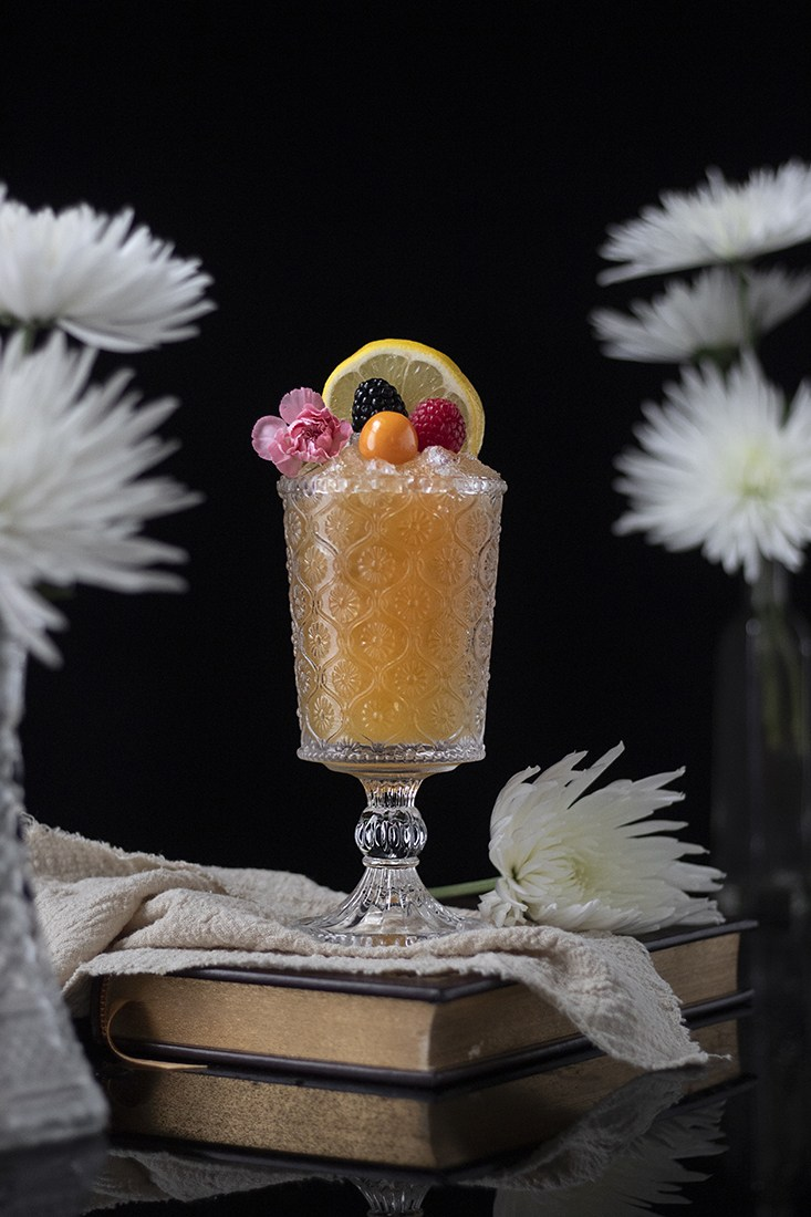 Earl Grey cobbler mocktail in tall vintage stemmed cocktail glass on top of towel & book next to white flowers