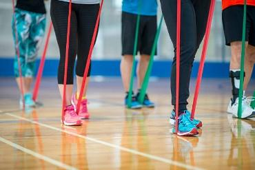 Fitness Class with Resistance Bands A group of adults are taking a fitness class at the gym. They are using resistance bands in their workout. The image is taken of the waist down. resistance bands stock pictures, royalty-free photos & images