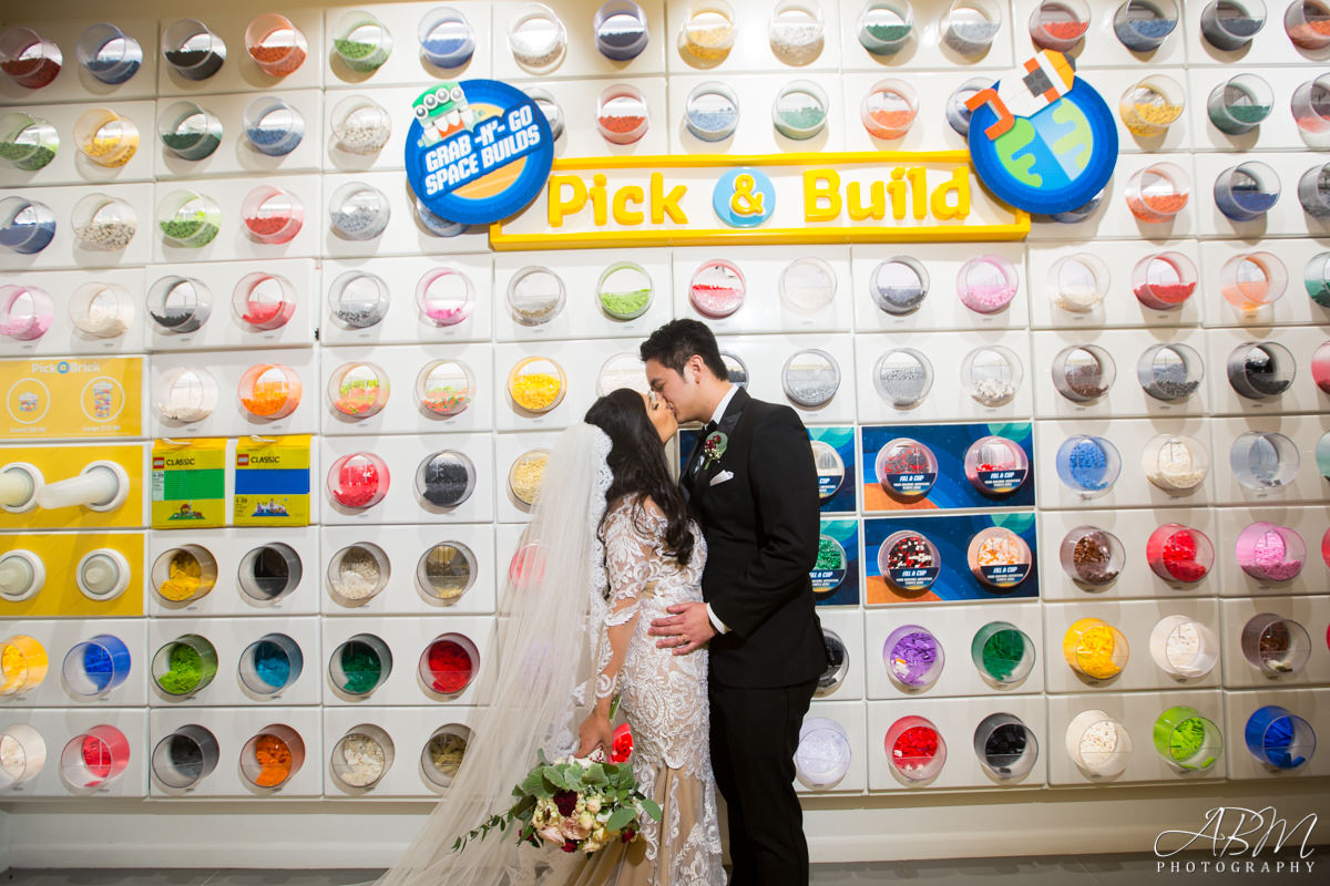 Newlyweds standing in front of a LEGO Pick-a-brick-wall