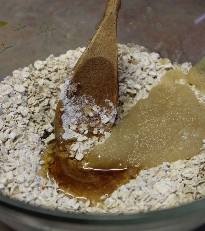 Flour, Oats, Honey, and Applesauce in a glass bowl with a wooden spoon | How to Make Simple Homemade Horse Treats | Mama on the Homestead