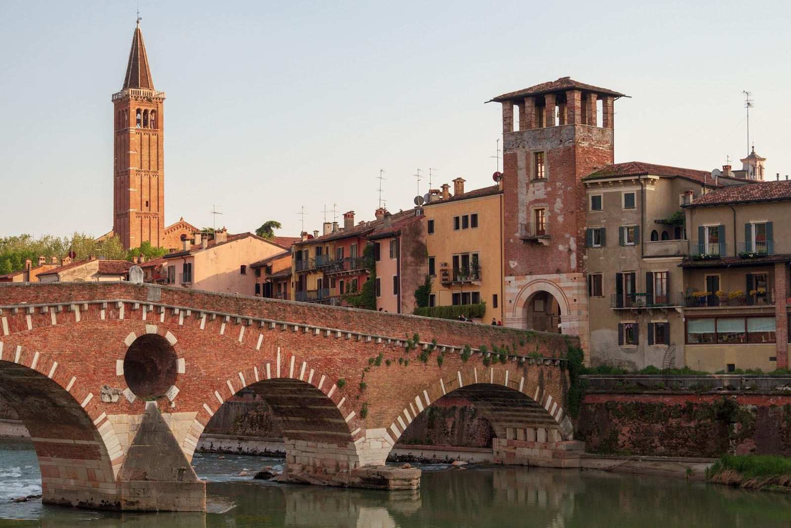 verona traditional historical town medieval stone buildings and bridge over adige river at sunset in italy. See Verona on an italy road trip