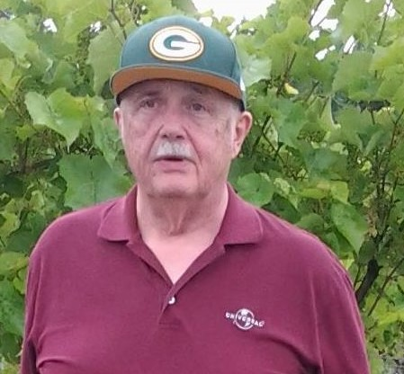 TOCtooler Jim Siewert, outside in front of a large bush, wearing a dark green cap with a Green Bay logo