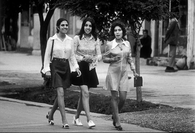 Tres jóvenes estudiantes afganas con moda de los 70 acuden a la universidad con el pelo suelto, minifalda y tacones.