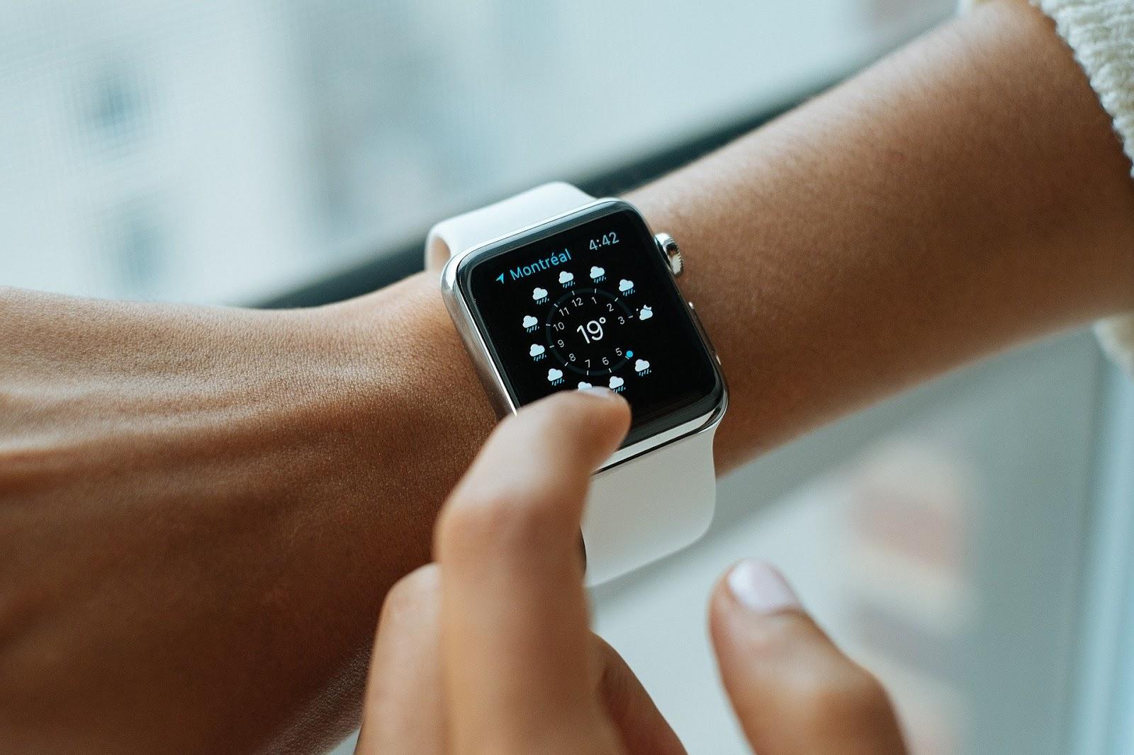 Uma mão apertando seu relógio.