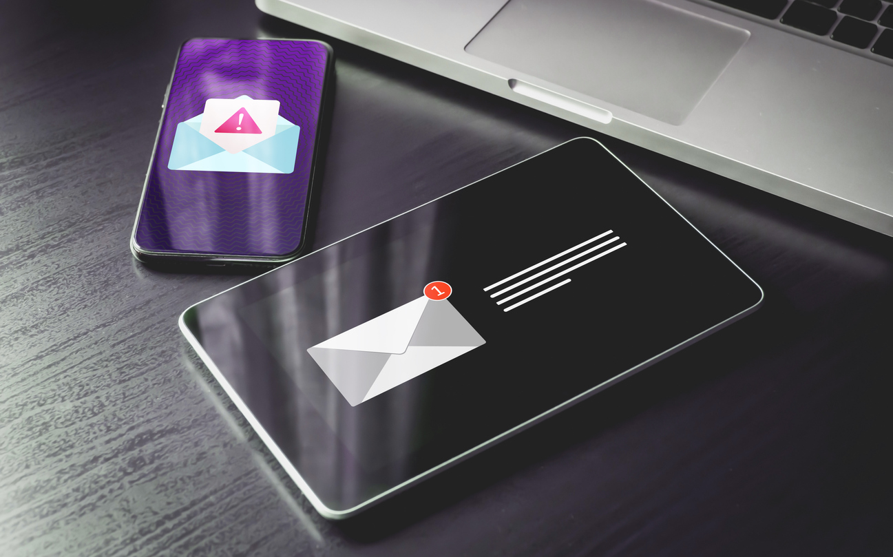 A smartphone, a tablet, and a laptop displaying email notifications to represent phishing scams, just one threat underlining the importance of multiple backups today.