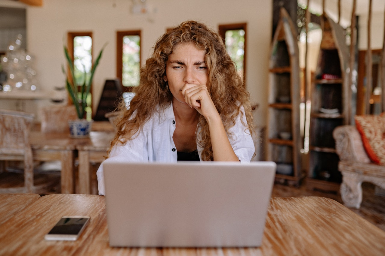 a person thinking and using a laptop