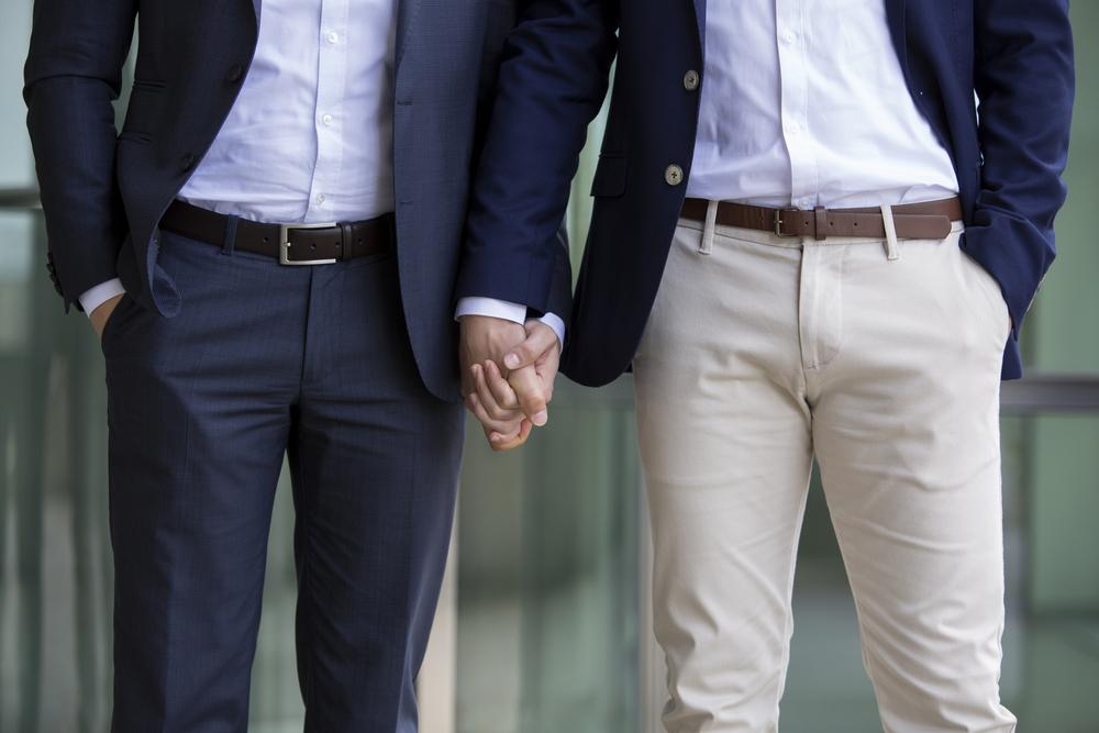 Dois homens dando as mãos de terno.