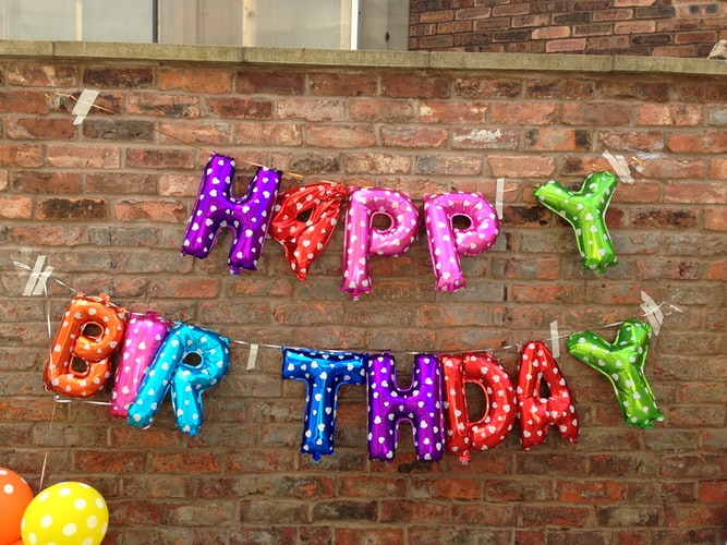 helium balloons spelling the words 'happy birthday' hanging on a brick wall