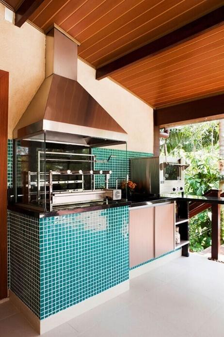Área externa de casa com churrasqueira e parede da pia revestidas de pastilhas verde, piso branco e teto de madeira.