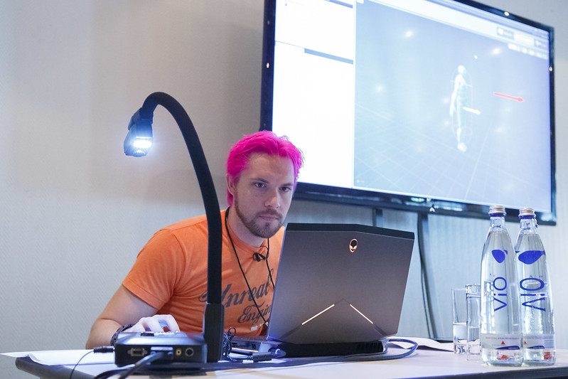 a man with pink hair and an orange Unreal t-shirt works with Unreal Engine