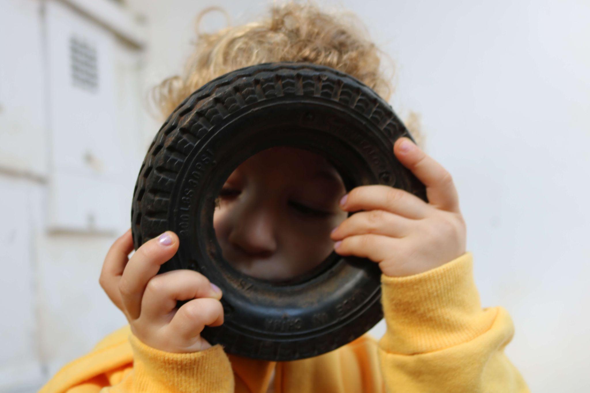 AS imagem mostra um criança olhando através de um brinquedo.