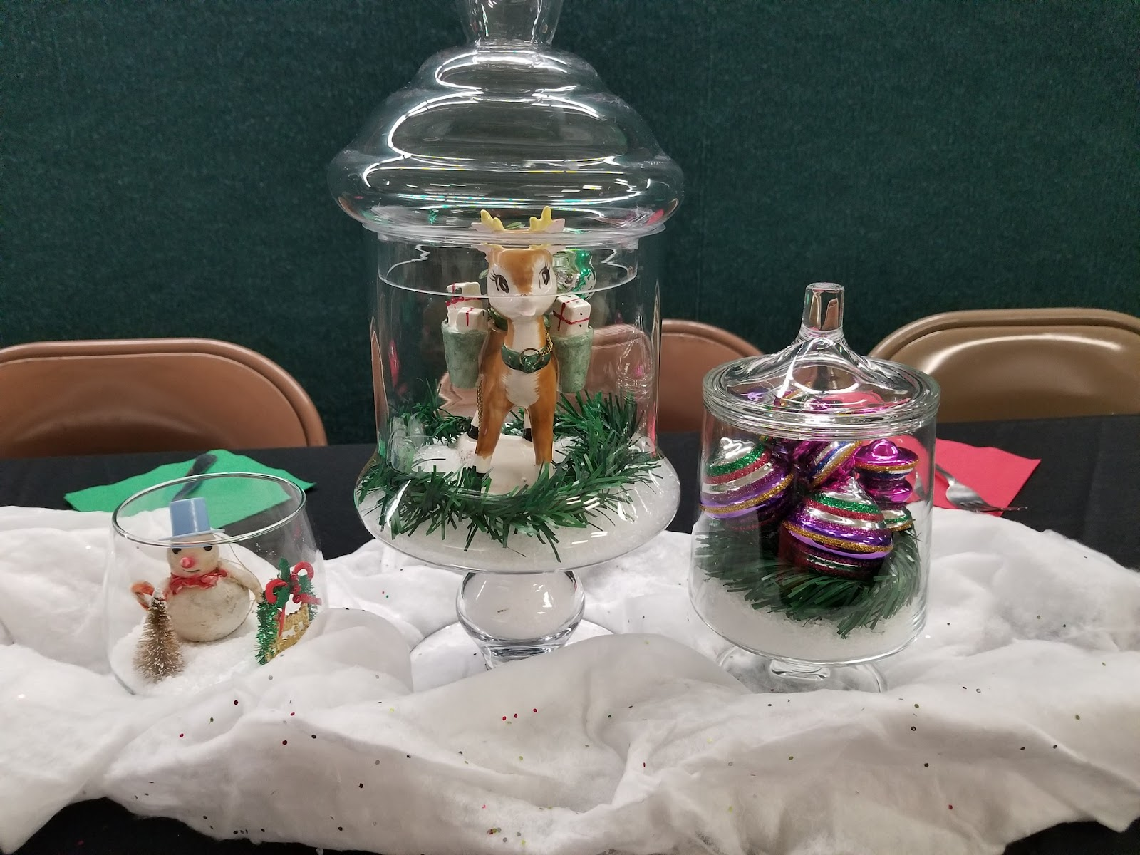 Several center pieces featuring holiday figurines like snowmen and reindeer sit on a table decorated with white fluff to look like snow.