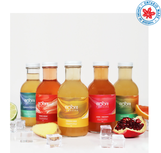 five bottles of moore kombucha with coloured labels in blue, red and yellow.  There is a piece of ginger, a lime, a slice of grapefruit, a chunk of pomegranate and some ice cubs in the foreground.