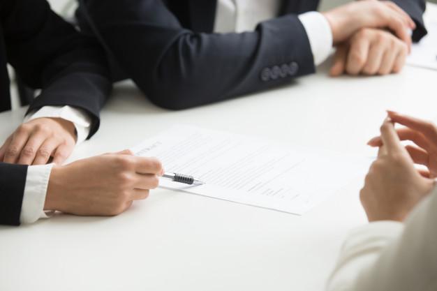 Homens de negócio discutindo sobre termos de um documento