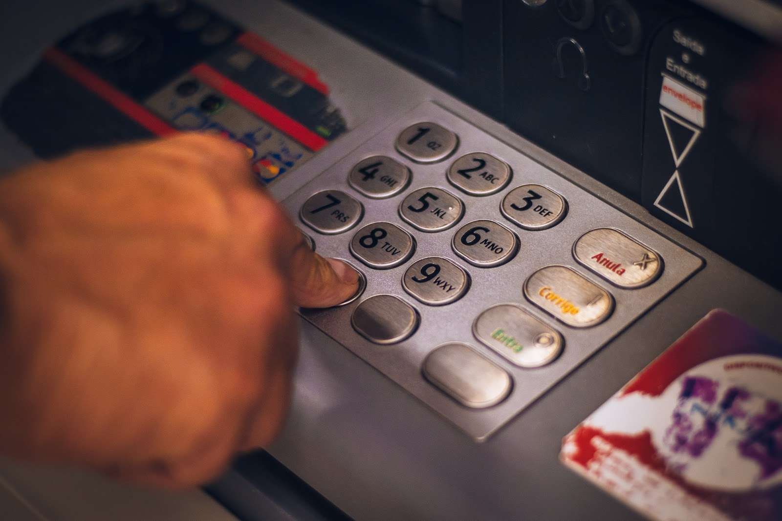 man pressing buttons on an ATM machine
