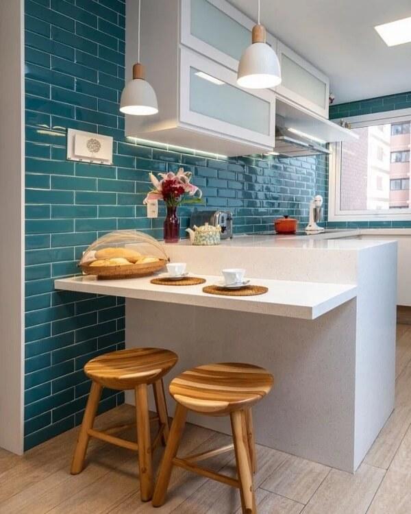 Cozinha com bancada branca, armários brancos, lâmpadas pendentes brancas, banco e piso de madeira e azulejo azul nas paredes.