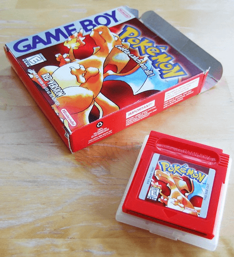 a nintendo game pokemon box and red game cartridge sitting on a light brown wooded table