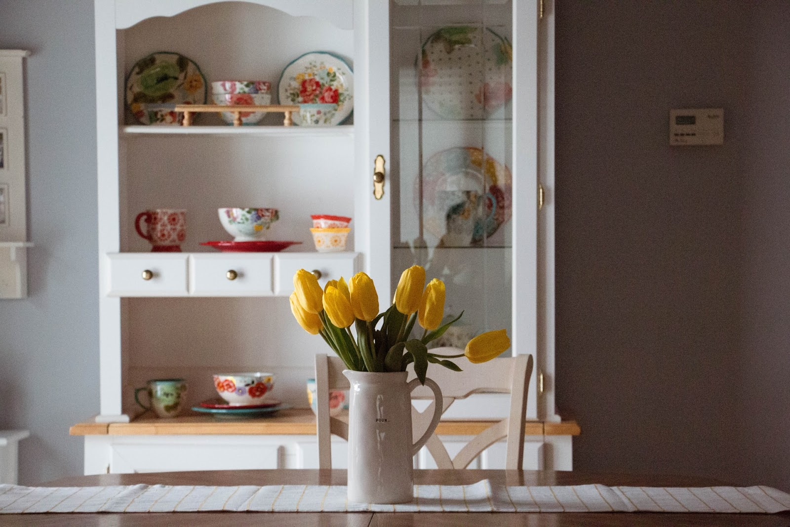 A vase full of fresh yellow tulips being used as a centrepiece on the table representing how you can integrate natural elements in your kitchen