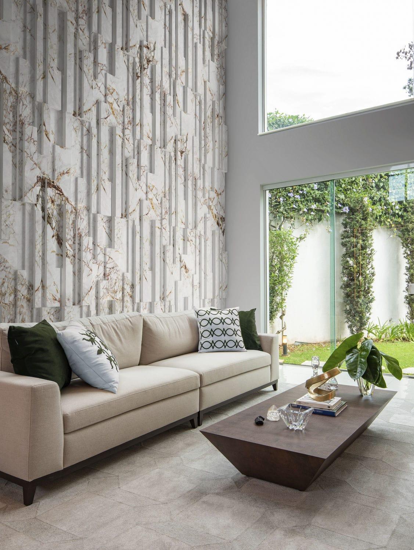 Sala com sofá nude com almofadas brancas e verdes, mesinha de centro de madeira, tapete em tom neutro e parede de fundo com revestimento 3D da linha Squadri Colors