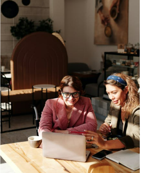 A couple of women sitting at a table looking at a book  Description automatically generated with medium confidence