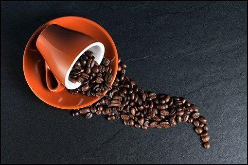coffee beans on orange ceramic mug