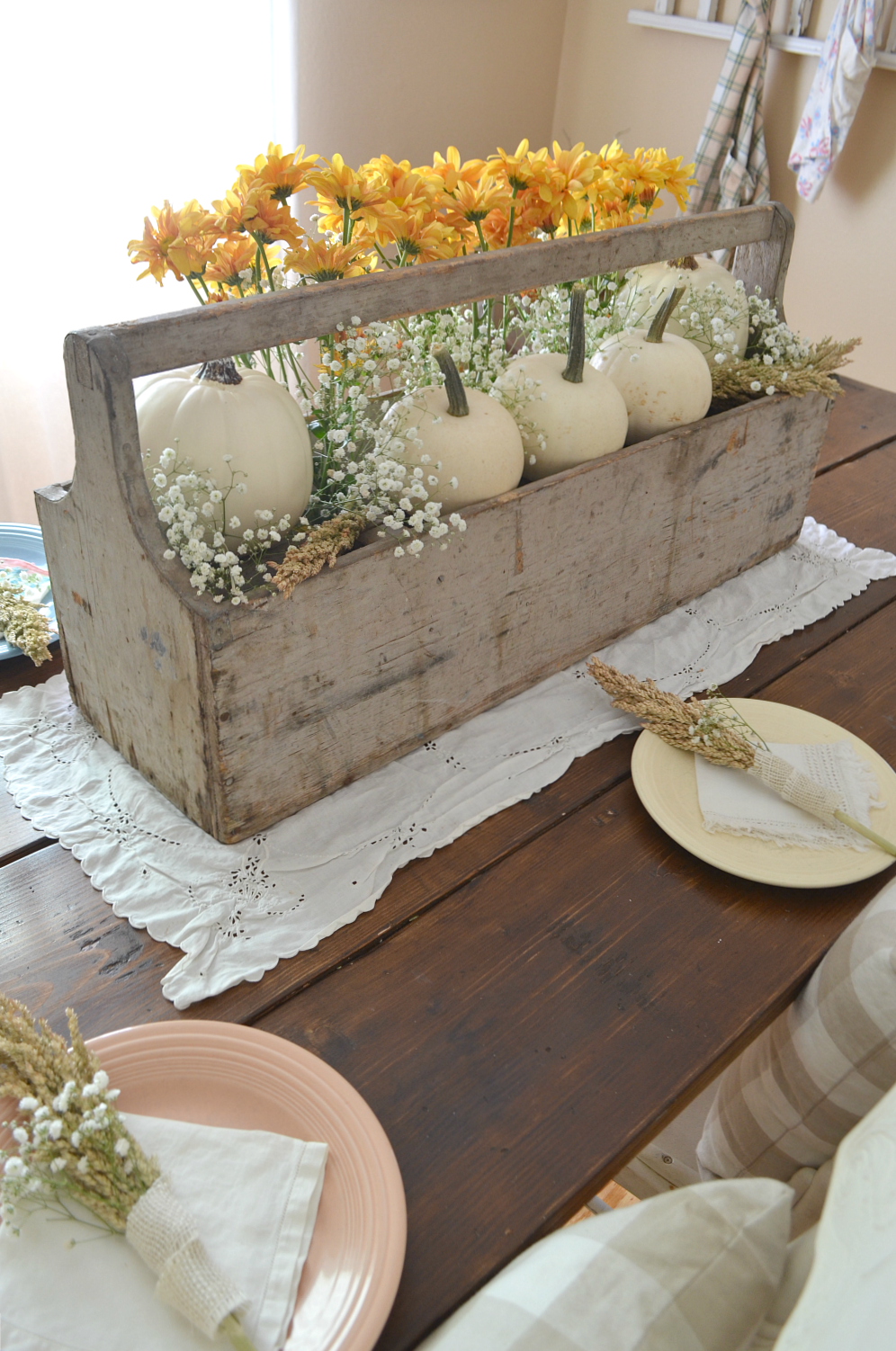 fall kitchen table centerpiece using old tool holder. contains five white pumpkins and white and yellow flowers