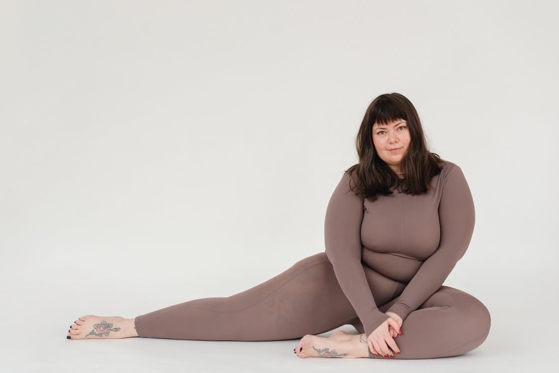 Overweight woman in activewear sitting in studio during training