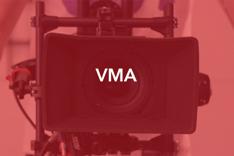 """An image of a film camera pointed at the viewer. Bold text is placed over the image. It reads: """"VMA""""."""