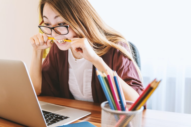 woman looking at laptop and biting down on a pencil.