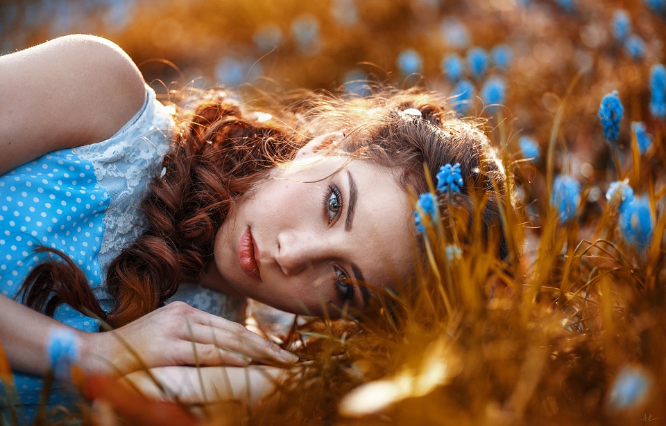 girl laying in golden field with blue flowers