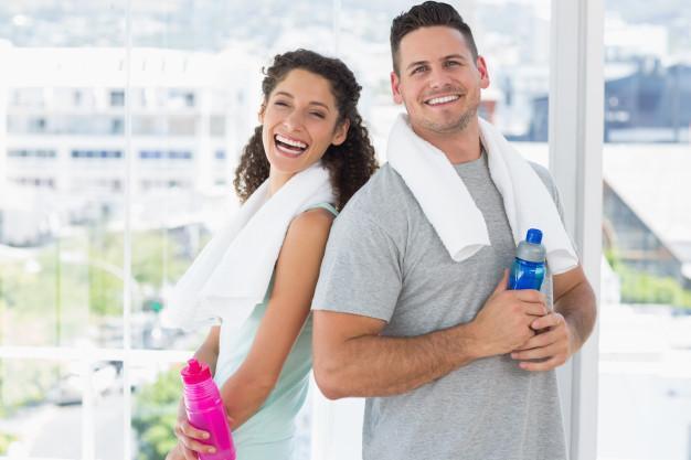 Casal com toalhas e garrafas de água na academia Foto Premium
