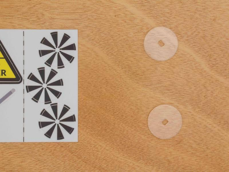 Black and white striped circular stickers on a sticker sheet, next to two flat clear discs with holes in the middle. The black and white stickers attach to the discs to make special encoder wheels for this wifi robot.