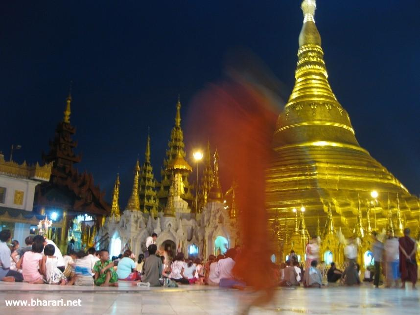 A monk walking past the magnificent Shwedagon Pagoda in Yangon, Myanmar