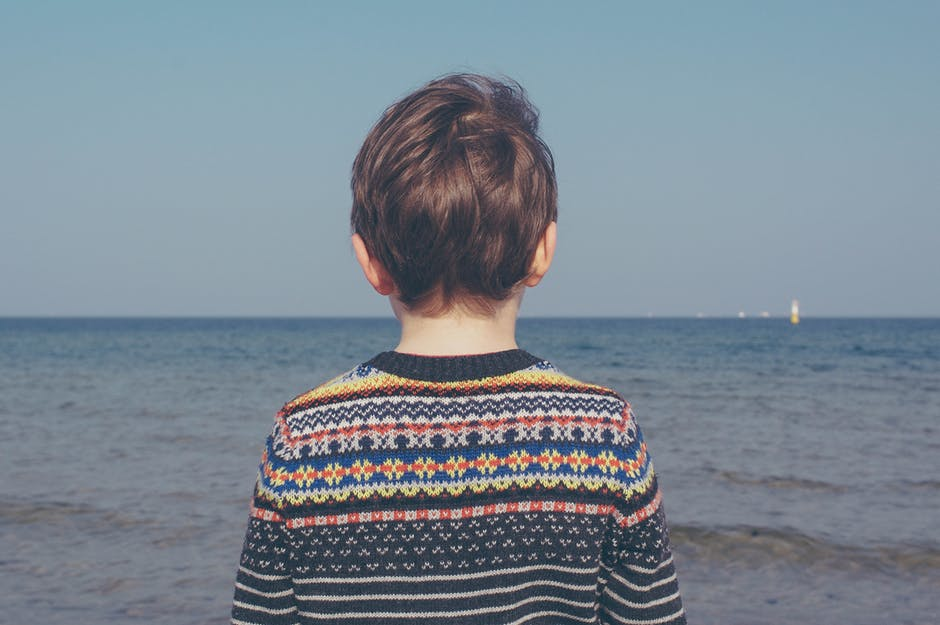 Boy in Black Blue White Sweater Near Shore during Daytime