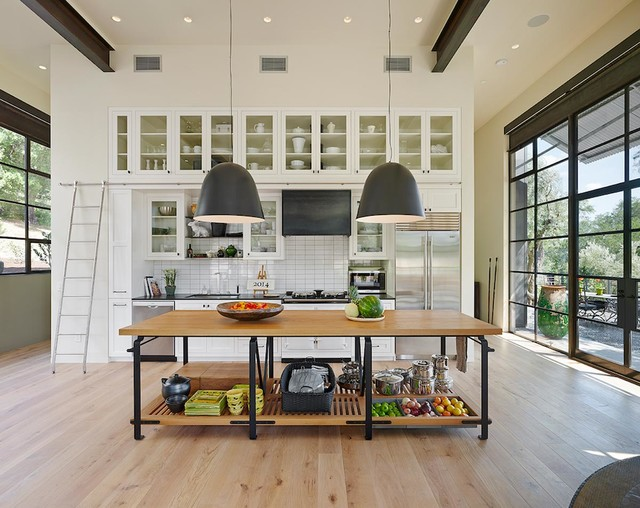 large bright california kitchen with wood island and white shaker cabinets