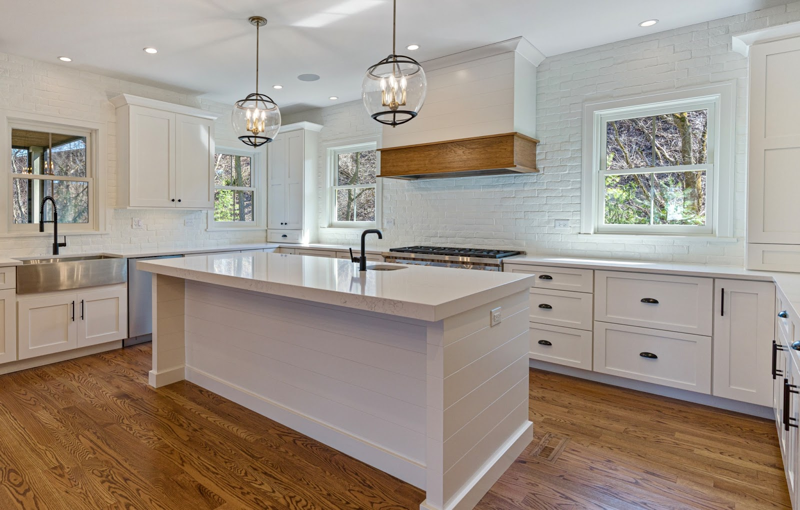 White kitchen with a natural wood accented range hood and white painted brick backsplash for added interest and texture. Featuring a stainless steel apron sink and appliances, black faucets and globe pendant lights above the kitchen island.