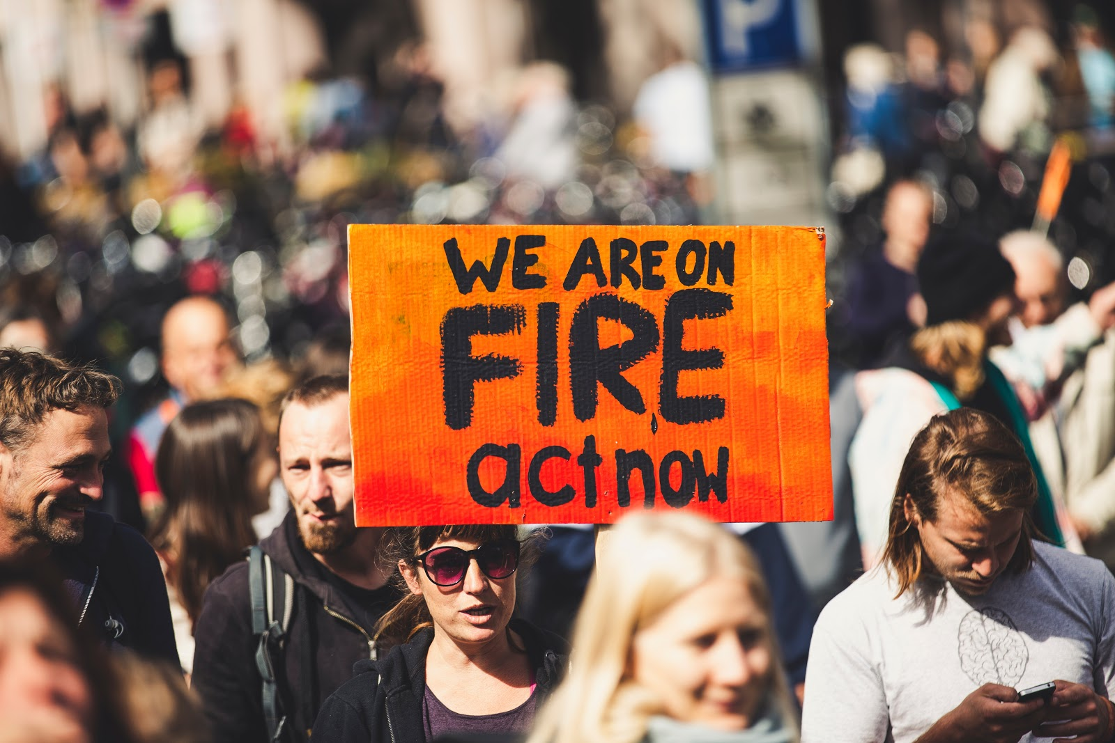 """woman with poster """"we are on fire, act now"""""""
