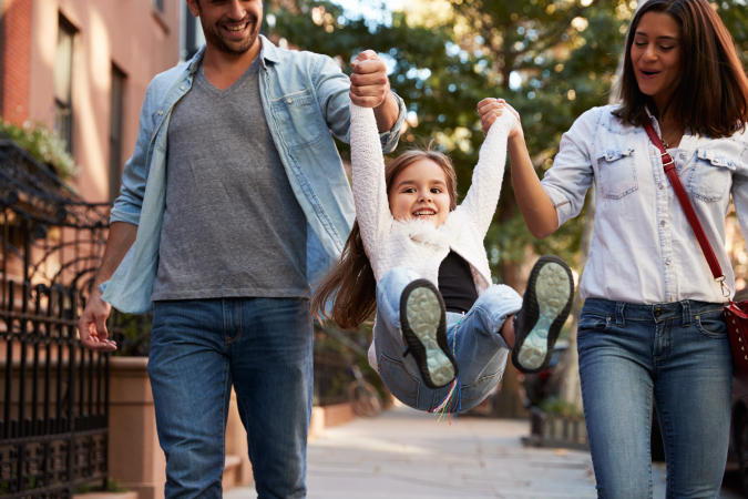 A mom and dad swinging their daughter while walking in a new city